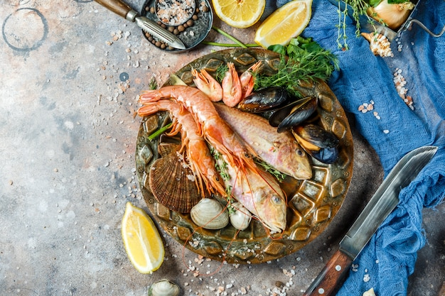 Bild von fischen, garnelen, muscheln auf keramikplatte am tisch mit zitrone, messer, muscheln