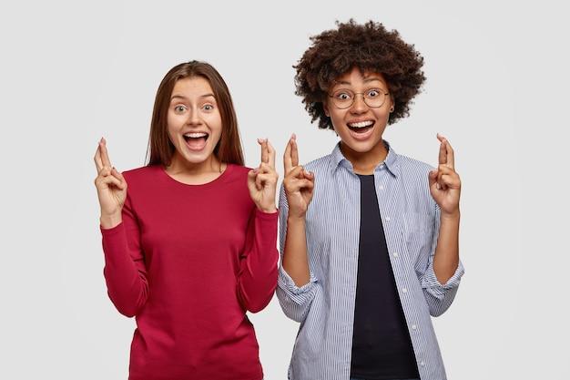 Bild von freudigen multiethnischen frauen halten hände mit gekreuzten fingern erhoben