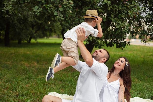 Bild von fröhlichen jungen kaukasischen frauen und männern hält ihr kind an den händen, lächelt und freut sich