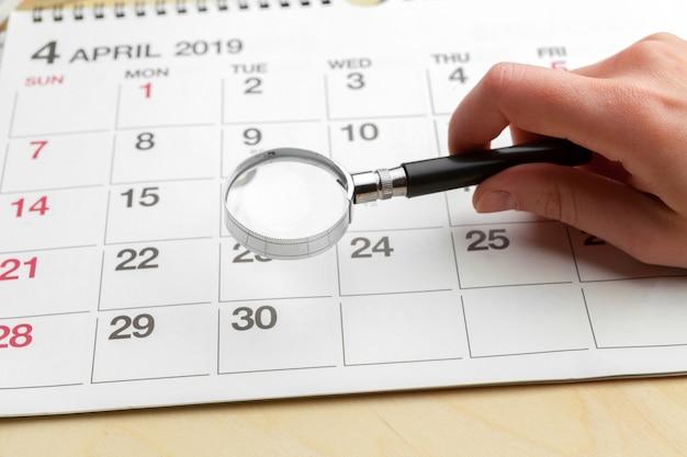 Bild von geschäft und tagungen. kalender zur erinnerung an einen wichtigen termin und lupe