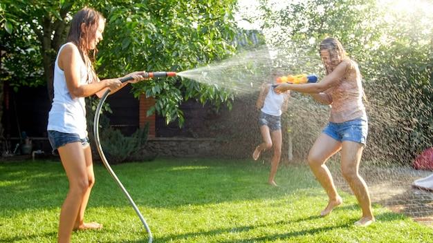 Bild von glücklichen kindern, die im garten des hauses mit wasserpistolen und gartenschlauch spielen. familie, die im sommer im freien spielt und spaß hat