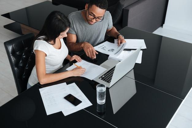 Bild von glücklichen liebenden jungen paaren, die laptop verwenden und ihre finanzen mit dokumenten analysieren. schauen sie sich papiere an.