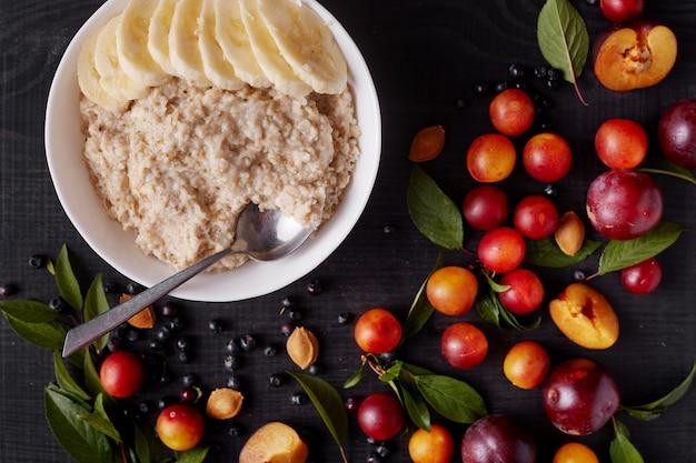Bild von haferflocken mit banane in der weißen platte lokalisiert über dunkler holzoberfläche, köstliches und gesundes frühstück für familie, frucht auf schwarzer tafel