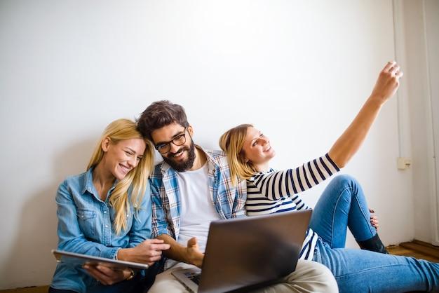 Bild von jungen baumstudenten, die auf boden sitzen und geräte halten. computer anschauen und telefonieren.