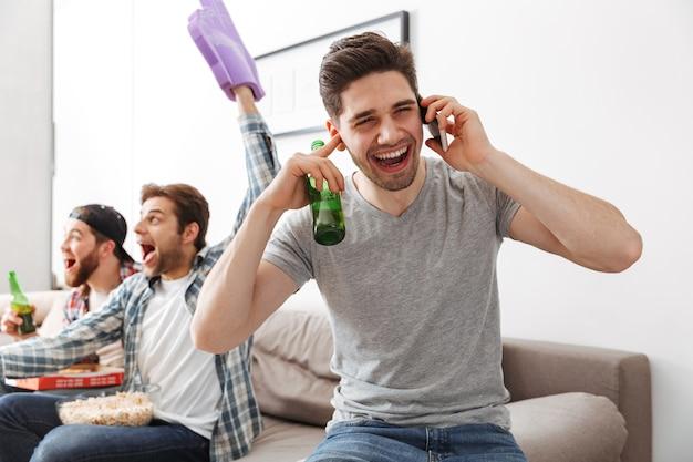 Bild von jungen junggesellen, die den sieg der lieblingsmannschaft feiern, während fußballspiel zu hause mit bier und snack zuschauen