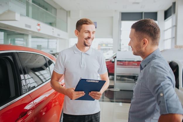 Bild von kunde und verkäufer stehen zusammen vor schönem rotem auto. sie sehen sich an und lächeln. verkäufer hält plastiktablette. sie sind im salon.