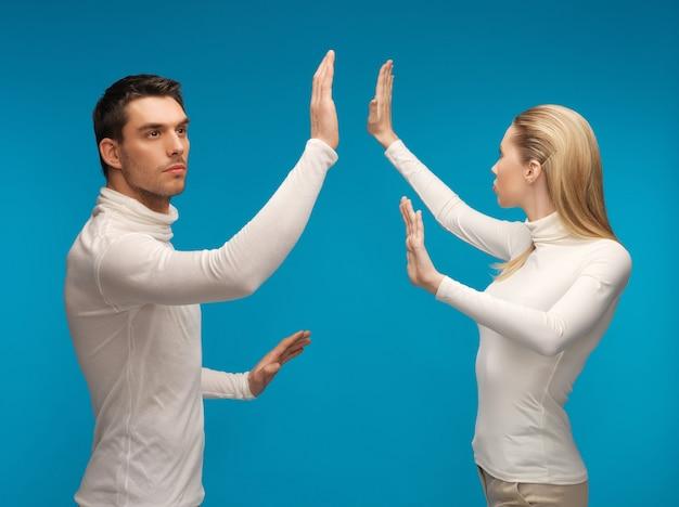 Bild von mann und frau, die mit etwas imaginärem arbeiten.