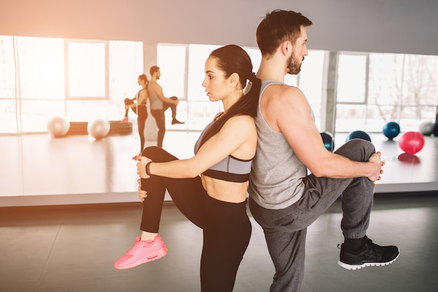 Bild von mann und frau, die rücken an rücken stehen und ein bein hochziehen. sie versuchen, das gleichgewicht der körper auf der einen seite zu halten.
