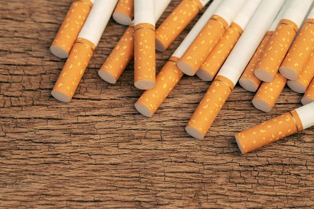 Bild von mehreren kommerziell hergestellten zigaretten. haufen zigarette auf holz. oder nichtraucherkampagnenkonzept, tabak