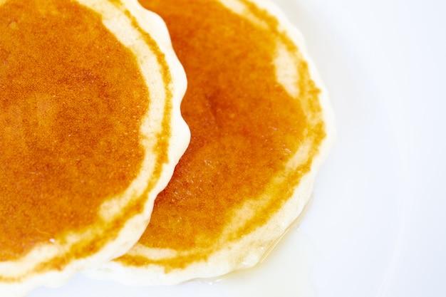Bild von pfannkuchen tropfte mit wildem honig auf einem tellerabschluß oben.