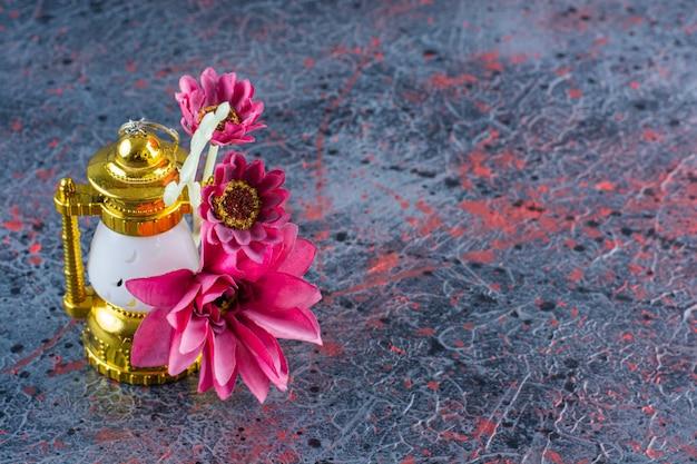 Bild von rosa blumen mit schöner lampe auf grau