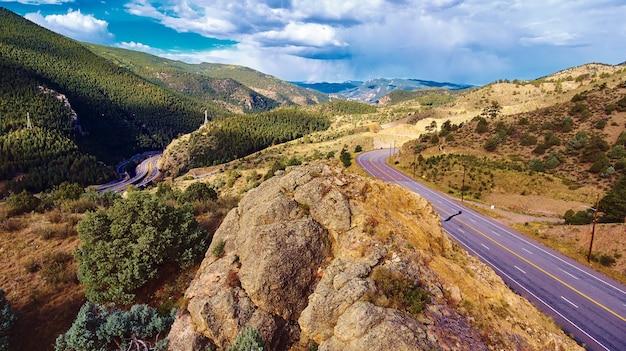 Bild von straßen durch die rocky mountains neben einem großen felsbrocken