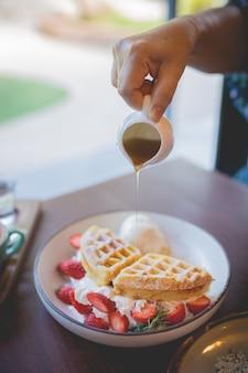 Bild von waffel-pfannkuchen-wüste mit vanilleeis, frischer erdbeere und honigsirup