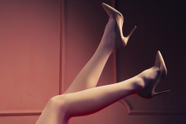 Bild von weiblichen beinen, die weiße strümpfe und ein bild mit hohen absätzen tragen
