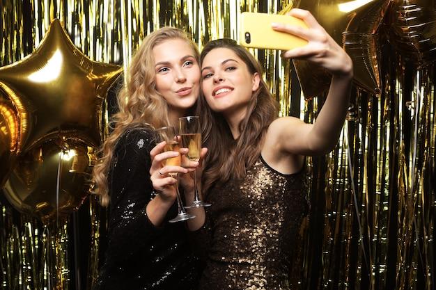 Bild von zwei attraktiven mädchen in stilvollem outfit, die smartphone halten und selfie-foto auf goldenem hintergrund machen.
