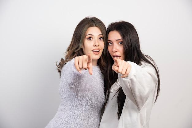 Bild von zwei besten freunden, die zusammen stehen und auf die kamera auf der weißen wand zeigen.