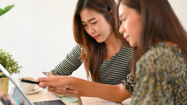 Bild von zwei geschäftsmitarbeitern, die mithilfe von smartphone- und tablet-teamwork zusammenarbeiten