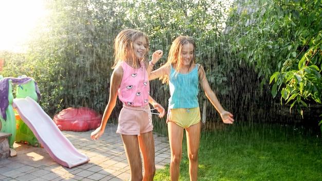 Bild von zwei glücklich lachenden mädchen im teenageralter, die unter warmem sommerregen im garten des hauses springen und tanzen. familie, die im sommer im freien spielt und spaß hat