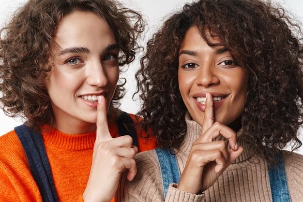 Bild von zwei glücklichen gemischtrassigen freundinnen in denim-overalls