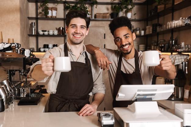 Bild von zwei glücklichen kaffeemännerkollegen in der cafébar, die drinnen arbeitet.