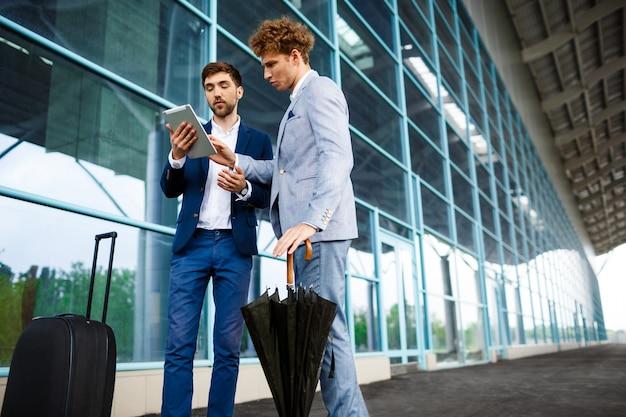Bild von zwei jungen geschäftsleuten, die am flughafen sprechen und tablette halten