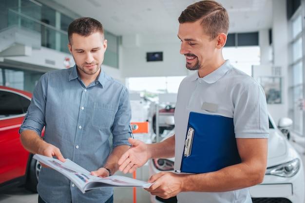 Bild von zwei männern, die innen stehen. sie halten ein tagebuch und schauen es sich an. die leute lächeln. sie stehen am roten auto. mann im weißen hemd zeigt auf tagebuch und lächeln.