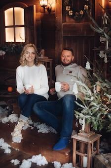 Bild von zwei schönen kaukasischen liebhabern in den gleichen pullovern, hosen und socken lächelt, die in weihnachten aufwerfen