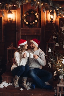 Bild von zwei schönen kaukasischen liebhabern in den gleichen pullovern, hosen und socken lächelt im wohnzimmer in weihnachten
