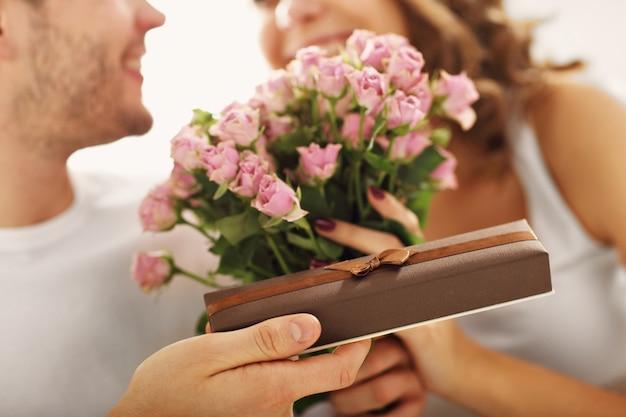 Bild zeigt einen mann, der einer frau im bett blumen gibt und ein geschenk macht