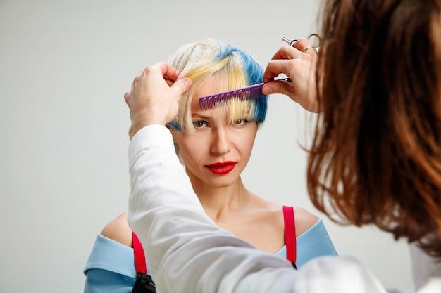 Bild zeigt erwachsene frau am friseursalon. studioaufnahme des anmutigen jungen mädchens mit stilvollem kurzem haarschnitt und buntem haar auf grauem hintergrund und händen des friseurs.