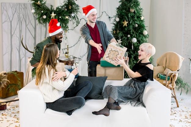Bild zeigt gruppe von freunden, die weihnachten feiern, die geschenke präsentieren