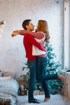 Bild zeigt junges paar, das über weihnachten umarmt und küsst
