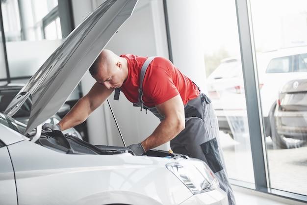 Bild zeigt muskulösen autoservice-arbeiter, der fahrzeug repariert.