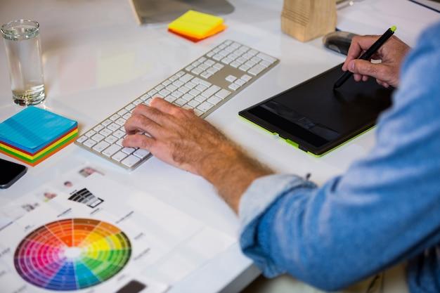 Bildbearbeitung, die am schreibtisch im kreativen büro arbeitet