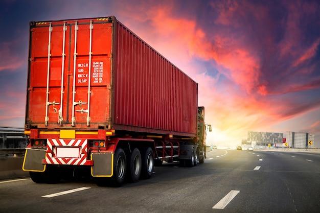 Bildbewegungsunschärfe. auf autobahnstraße mit rotem container, transportkonzept getroffen., import, exportlogistikindustrietransport landtransport auf der asphalt-schnellstraße mit sonnenaufgangshimmel.