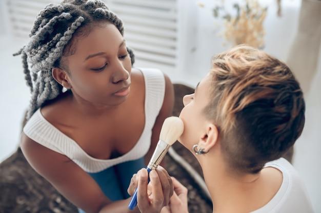Bilden. afroamerikanermädchen macht make-up zu ihrer freundin