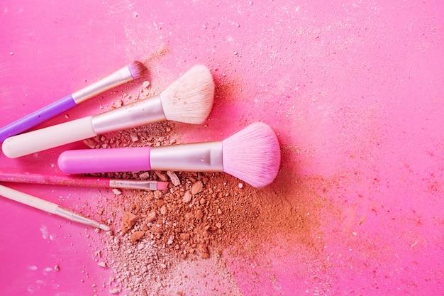 Bilden sie bürsten mit puder auf rosa hintergrund