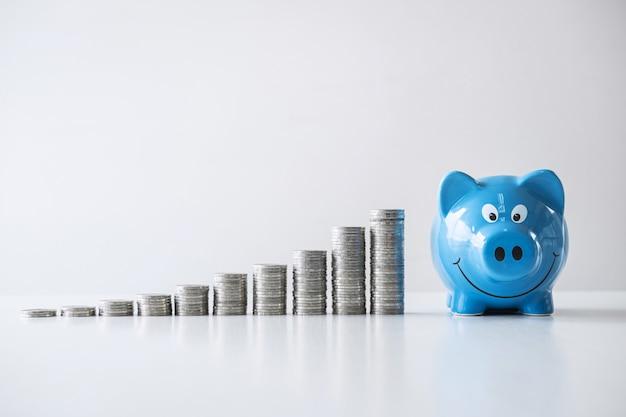 Bilder des stapelns des münzenstapels und des blauen lächelnden sparschweins zum wachsen und der einsparungen mit geldkasten, einsparungsgeld für zukünftigen plan und pensionskassenkonzept