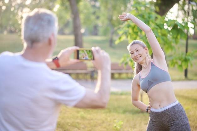 Bilder machen. ein mann macht ein foto von seiner frau, während sie trainiert
