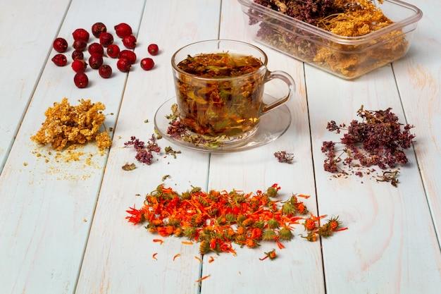 Bilder von kräuterpräparaten. frisch gebrühter tee aus heilkräutern. getrocknete heilkräuter für die gesundheit. lobaznik gewöhnlich, oregano, ringelblumenblumen, hagebutte auf einem holztisch. phytotherapie.