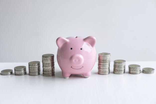 Bilder von stapelmünzen stapeln und rosa lächelndes schweinchen.