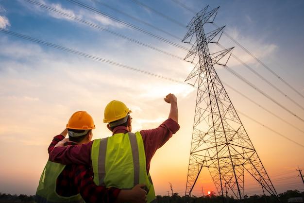 Bilder von zwei elektrotechnikern, die am kraftwerk stehen, um erfolg zu sehen und sich zu freuen. mit der erzeugung von elektrischem strom