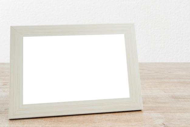 Bilderrahmen aus holz auf tisch mit weißer wand konkrete textur hintergrund.