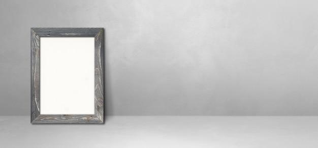 Bilderrahmen aus holz, der sich an eine hellgraue wand lehnt. leere mockup-vorlage. horizontales banner