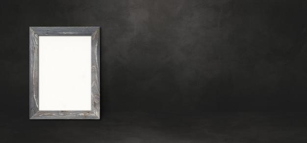 Bilderrahmen aus holz, der sich an eine schwarze wand lehnt. präsentationsmodellvorlage. horizontales banner