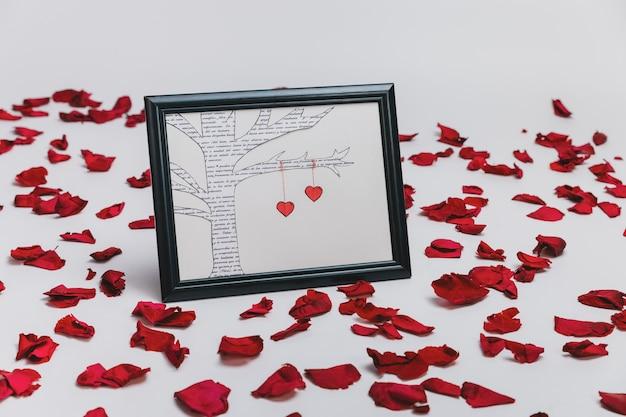Bilderrahmen mit einem gezogenen baum und rosenblättern um