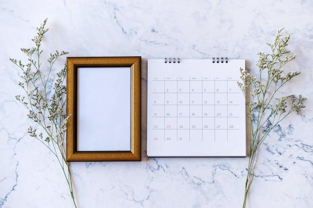 Bilderrahmen und kalender und kaspienblume auf marmor