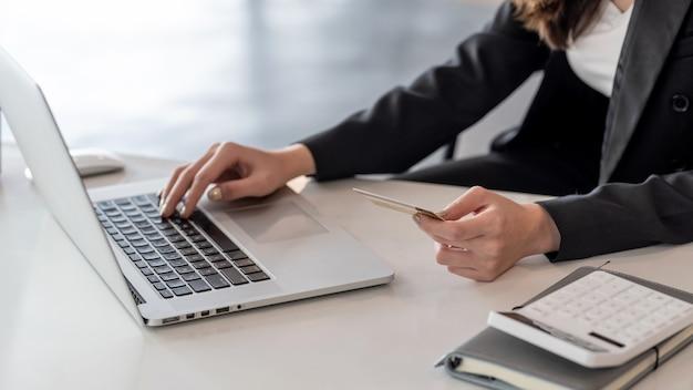 Bildhandgeschäftsfrau, die eine kreditkarte mit einem laptop im büro hält.