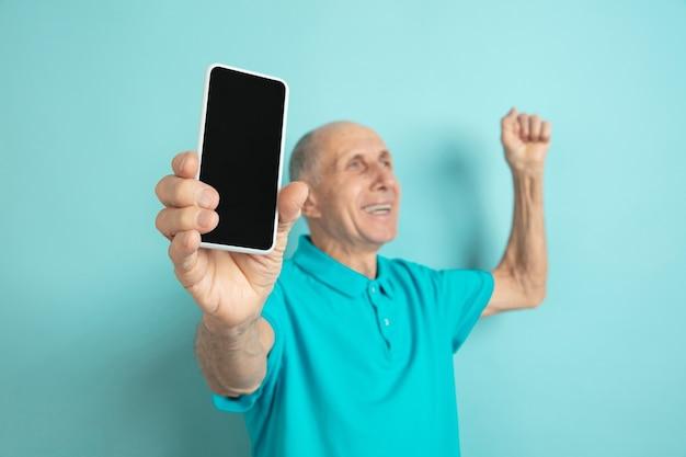 Bildschirm des leeren telefons anzeigen. porträt des kaukasischen älteren mannes auf blauem studio.