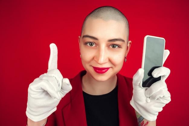 Bildschirm des leeren telefons. porträt der jungen kaukasischen kahlen frau lokalisiert auf roter studiowand.